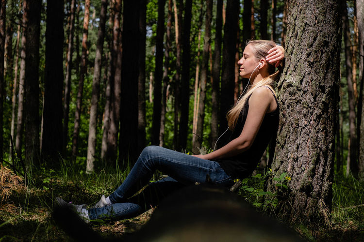 A girl in a forest sits leaning against a tree, with headphones listening to music. digital detox.