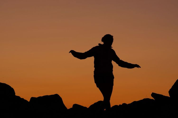 Silhouette woman standing on rock against sky during sunset