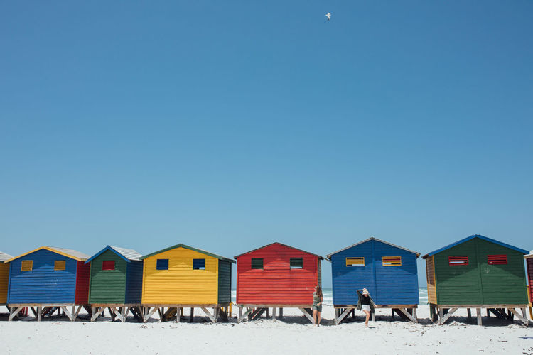 Women walking by beach huts against clear blue sky