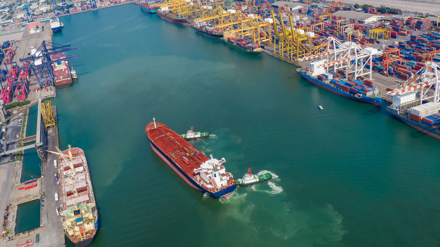Aerial top view tugboat drag oil red ship tanker to dock for load and unloading and shipping