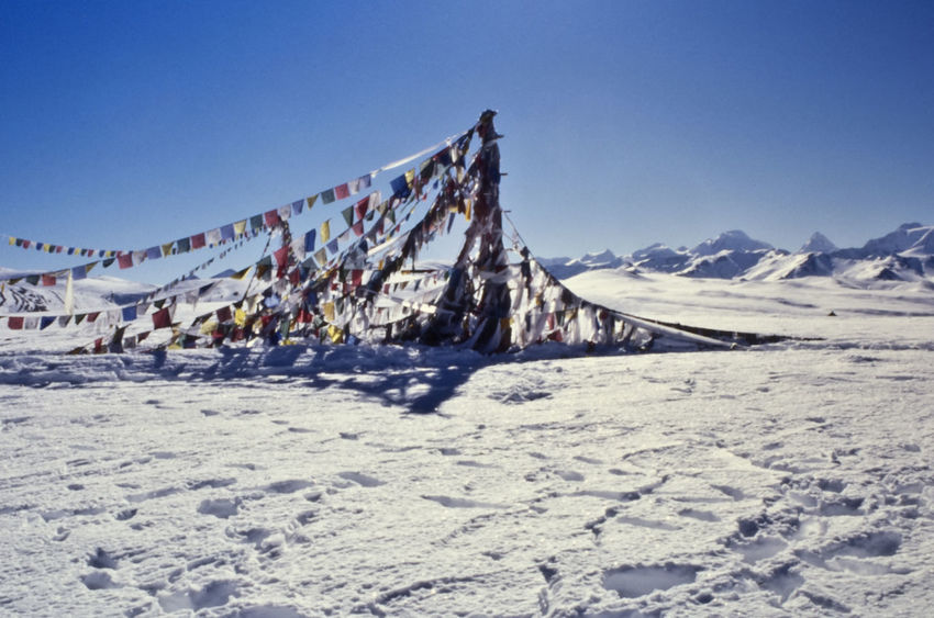 Beauty In Nature Blue Clear Sky Cold Temperature Day Flag Ice Landscape Mountain Mountain Pass Nature No People Outdoors Sky Snow Sunlight Tibet Tibetan  Tibetan Prayer Flags Winter Winter
