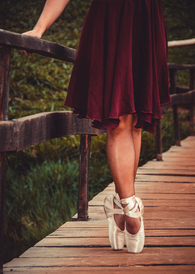 Low Section Of Woman Wearing Ballet Shoe Standing On Footbridge