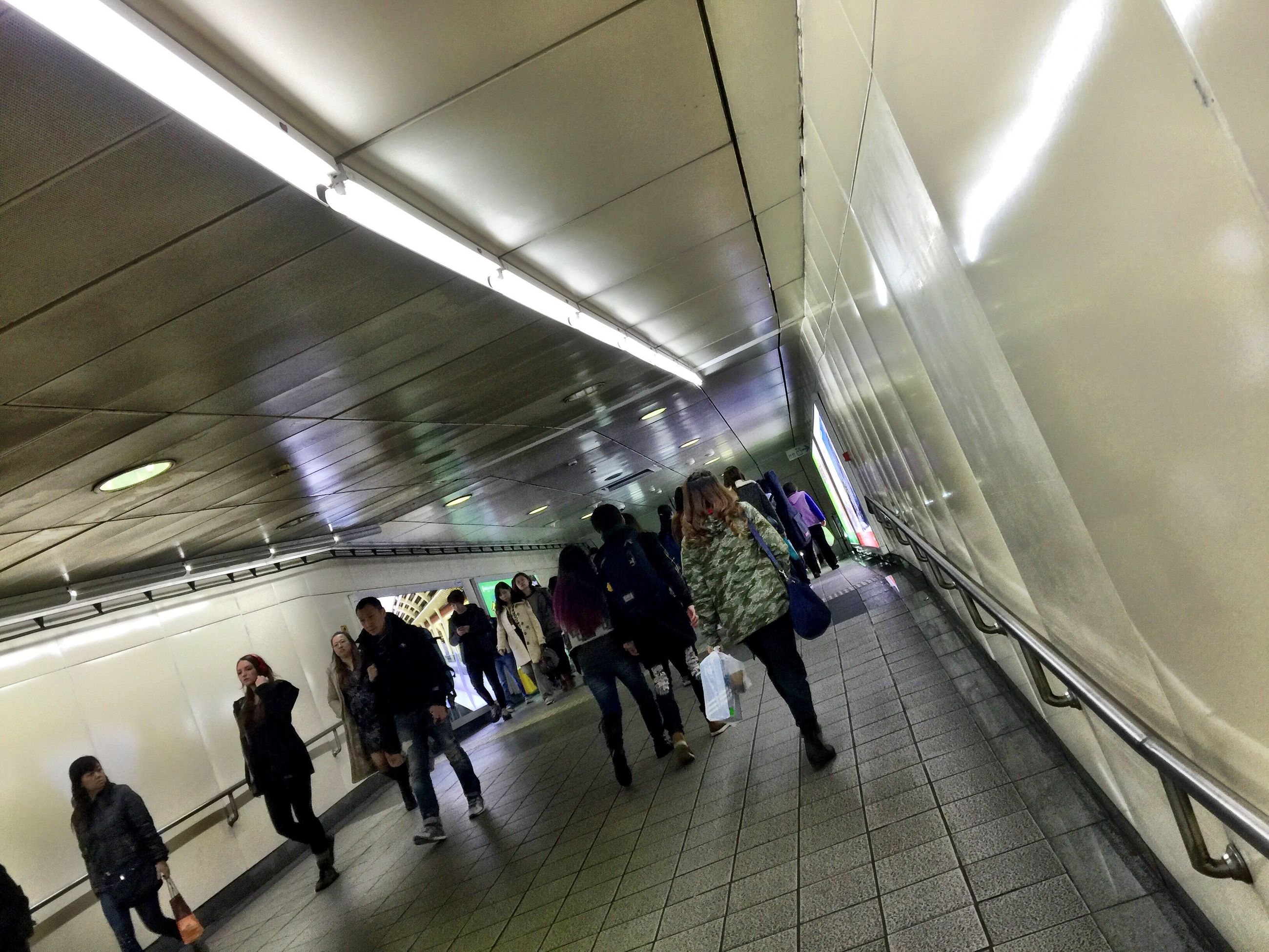 indoors, men, transportation, person, illuminated, lifestyles, large group of people, ceiling, walking, travel, subway station, the way forward, escalator, leisure activity, subway, mode of transport, lighting equipment, on the move, medium group of people