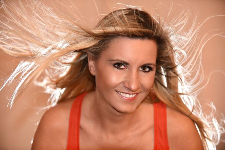 Portrait of smiling young woman with blond hair against brown background