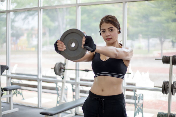 Portrait Of Woman Standing Exercising In Gym