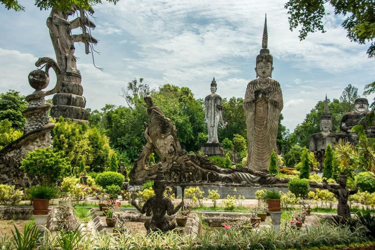 Old Buddha Statues At Sala Keoku Against Cloudy Sky