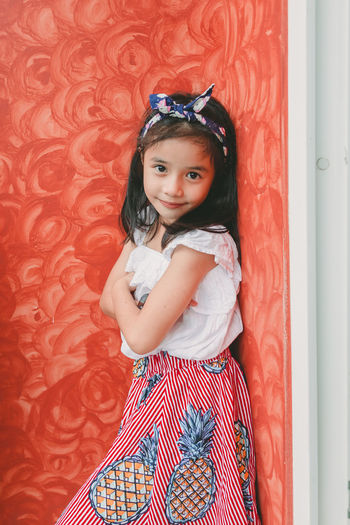 Portrait of cute girl standing against red wall