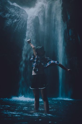 Woman with arms outstretched standing against waterfall
