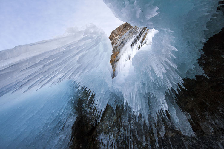 Icicles on snow covered mountain against sky