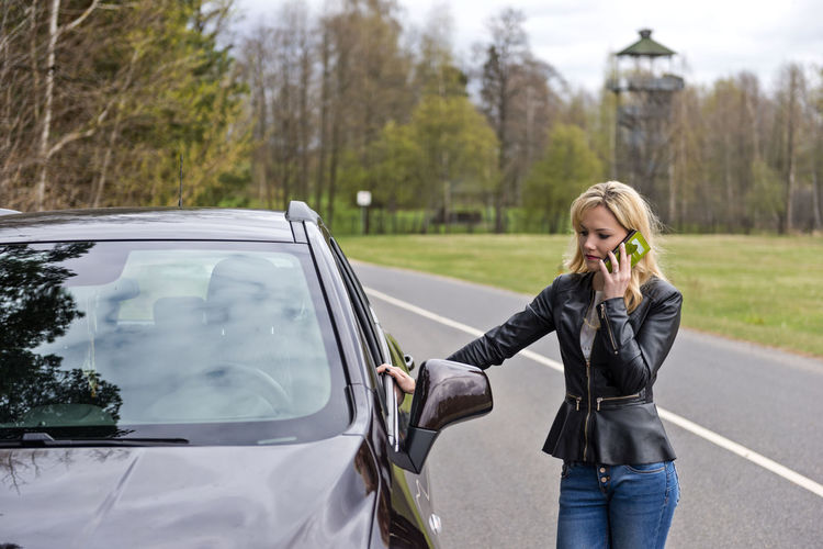 Woman using smart phone while standing by car