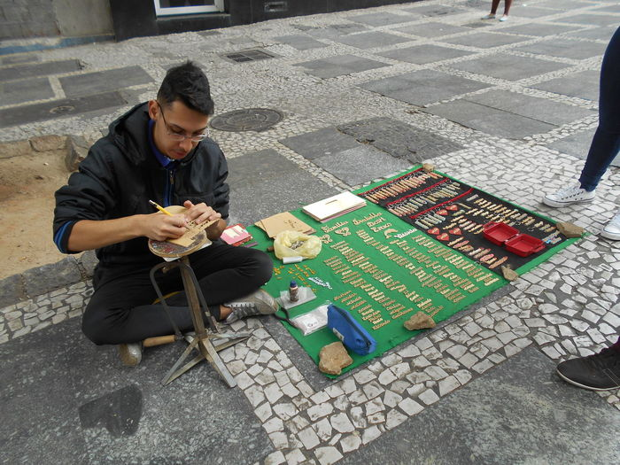 "Susan´s Series: Street Vendors in Downtown São Paulo (often referred to as a ""Micro-Empresa"", or Micro-Business) . ""Personalized Keychains"" Sr. Rodnei calmly carves a person´s name out of a thin piece of plywood laminate and turns it into a personalized keychain. He can be found at Rua XV de Novembro in downtown São Paulo. Mr. Rodnei provided verbal permission to take his photograph; like many street vendors, has no email. In the event this photo ever gets licensed I will be splitting the proceeds with Mr. Rodnei. He is a regular at this spot in downtown São Paulo, persistently plying his trade day in and day out to his customer´s satisfaction. Arts And Crafts City Life Sidewalk Small Business Heroes Street Vendor Susan A. Case Sabir Unretouched Photography City Day Downtown São Paulo Keychains  Micro-business Microempresa Outdoors Real People Selling On The Street Sitting Street Street Photography Urban Photography"