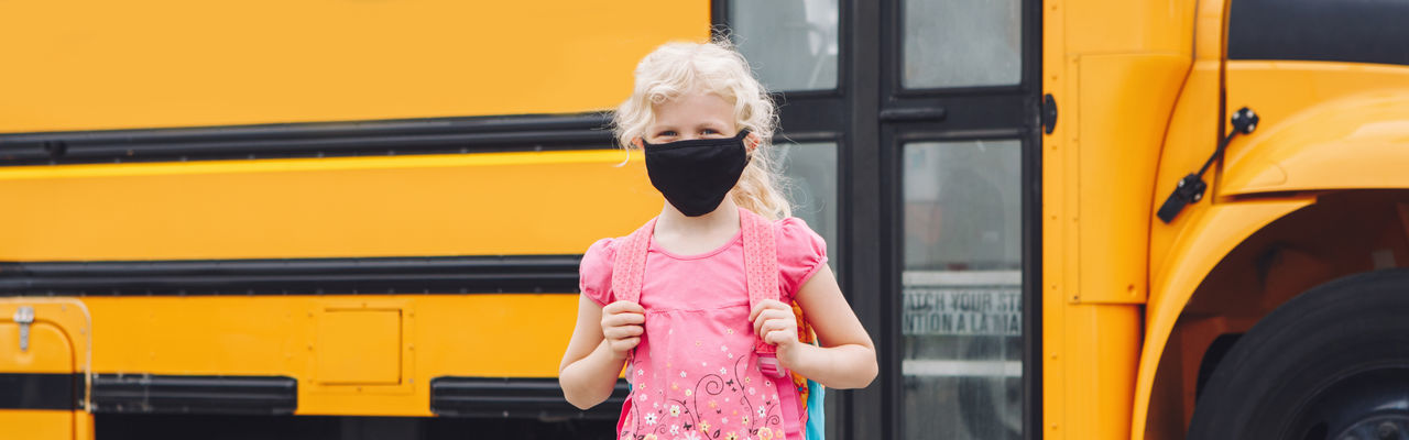 Back to school. girl student wearing face mask near yellow bus. web banner header.