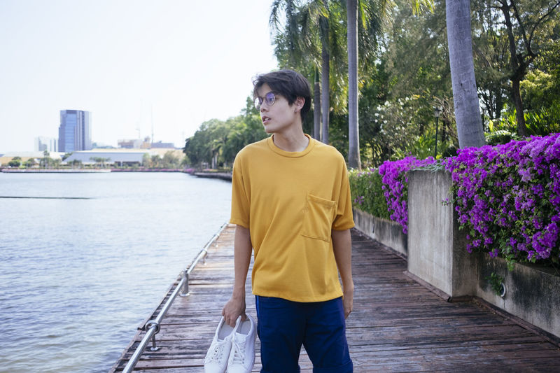 Young man looking away while standing on boardwalk by lake