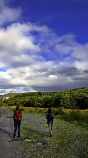 Rear view of hikers walking on field against sky