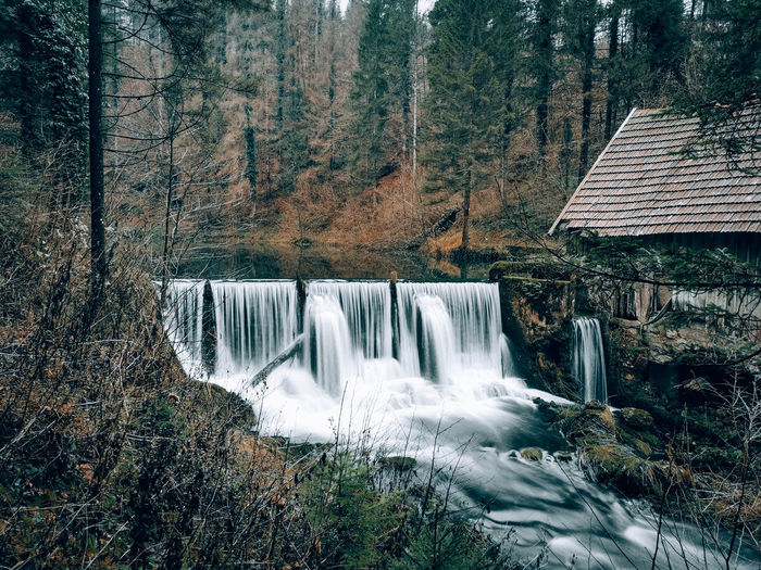 Long exposure image of waterfall in moody forest.