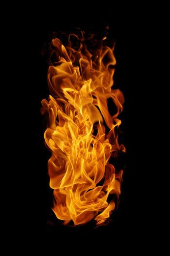 Close-up of orange burning against black background