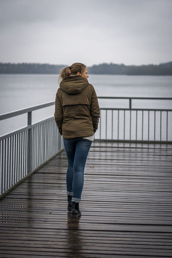 Rear view of woman walking on pier over lake against sky