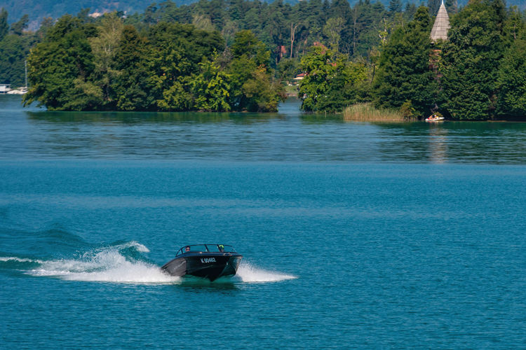 WORTHERSEE, AUSTRIA - AUGUST 08, 2018: View from the boat to the lake and coastline. Local residents and tourists swim, driven by motorboats and use other forms of water recreation. Nature Day Outdoors Austria Carinthia Carinthian Lakes Tourist Tourists Lake Wörthersee Recreation  Leisure Landscape Water Sea Boats Motorboat Speedboats Summer People Holidays Fun Travel Beach Resort Lifestyle Sunny Rest Joy Waves Europe Alps Alpine Alpine Lake Nautical Vessel Tree Transportation Mode Of Transportation Plant Waterfront Motion Beauty In Nature Scenics - Nature Wake - Water Wave Pattern Non-urban Scene No People