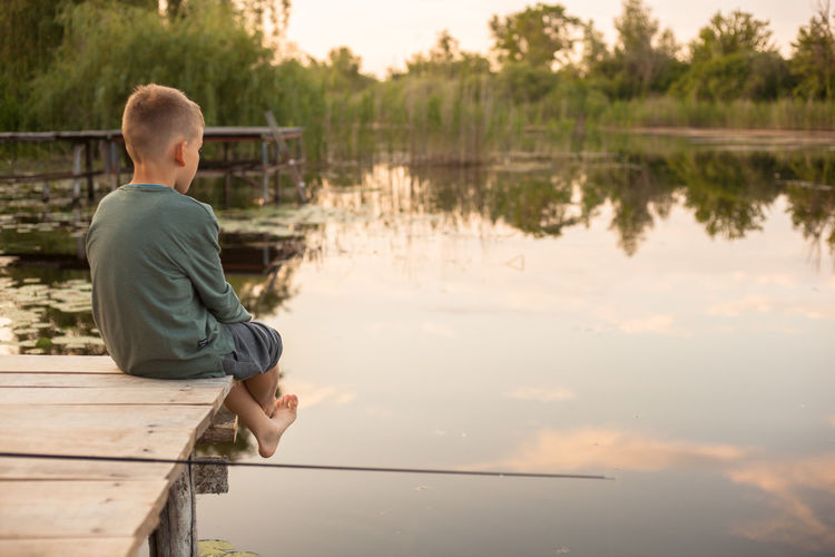 Rear view of boy sitting on pier over lake