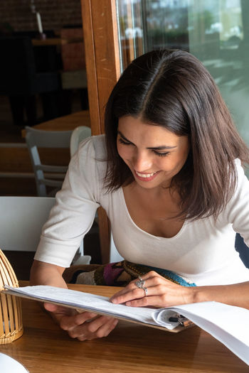 High angle view of smiling woman looking at menu while sitting on table in restaurant