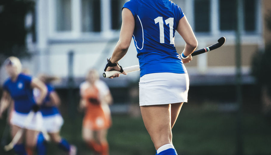 Young hockey player woman with ball in attack playing field hockey game Field Hockey Review Field Hockey Woman Active Athlete Ball Clothing Competition Competitive Sport Day Focus On Foreground Group Of People Incidental People Lifestyles Men Midsection Outdoors People Playing Real People Rear View Running Sport Sports Clothing Sports Uniform Sportsman Team