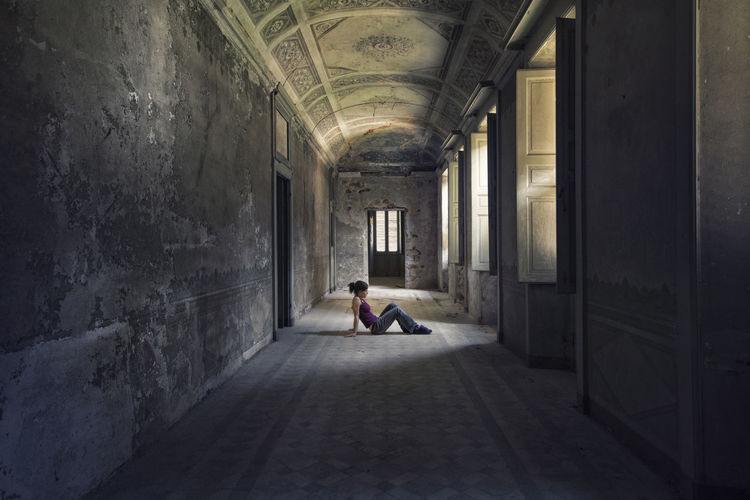 Rear view of man sitting in corridor of building