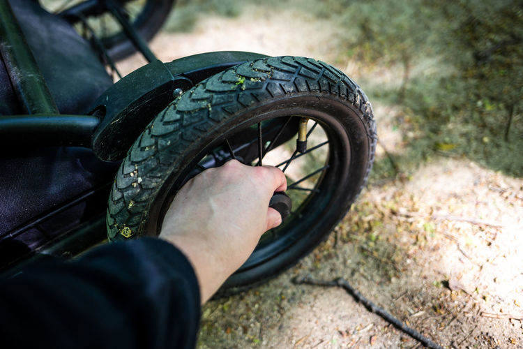 Close-up of man touching tire of baby stroller
