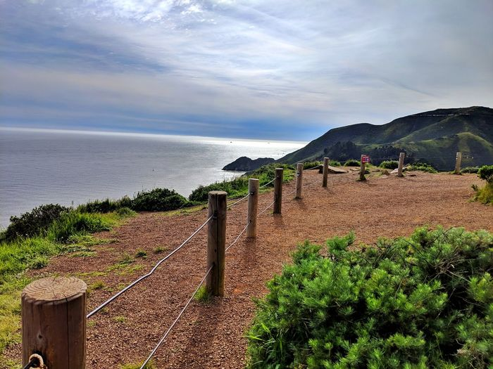 Cabled barrier posts rim overlook. Pacific ocean. Marin Headlands. Background. Reflected Light Blue Golden Intense Dramatic Headlands Cabled Posts Barrier Safety Overlook Curved  Ocean Background Dirt Peaceful Soil Sea Water Sky Horizon Over Water Cloud - Sky Rock Formation Coast Physical Geography Dramatic Sky Geology Seascape Eroded Sandstone Cliff Stay Out Springtime Decadence The Mobile Photographer - 2019 EyeEm Awards The Great Outdoors - 2019 EyeEm Awards The Traveler - 2019 EyeEm Awards My Best Photo