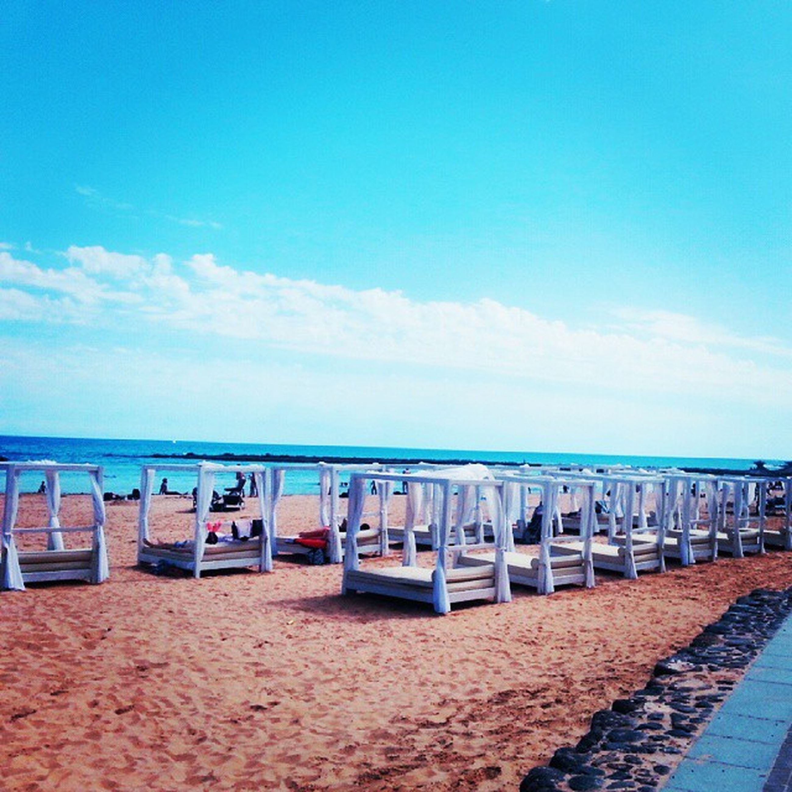 beach, sea, sky, sand, horizon over water, water, shore, blue, in a row, empty, tranquil scene, tranquility, day, nature, incidental people, cloud - sky, cloud, lounge chair, absence, scenics
