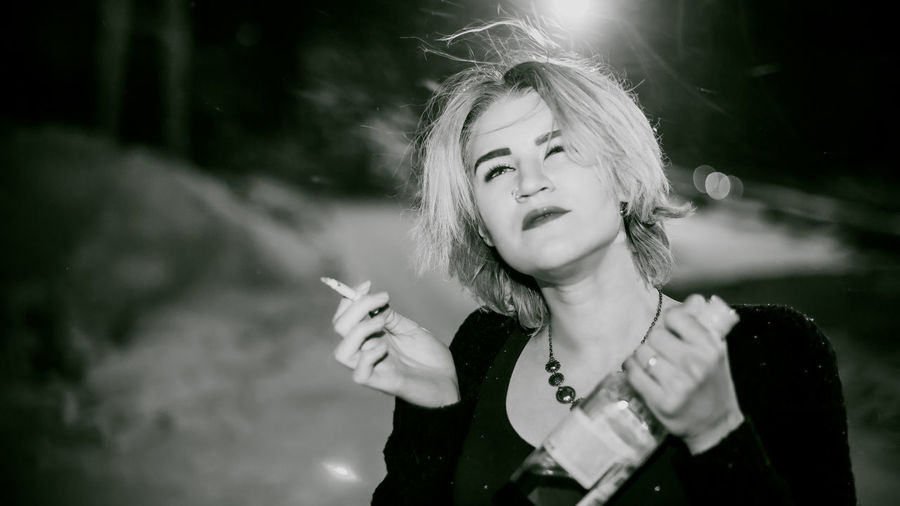 Close-Up Of Young Woman Smoking Cigarette While Holding Alcohol Bottle At Night