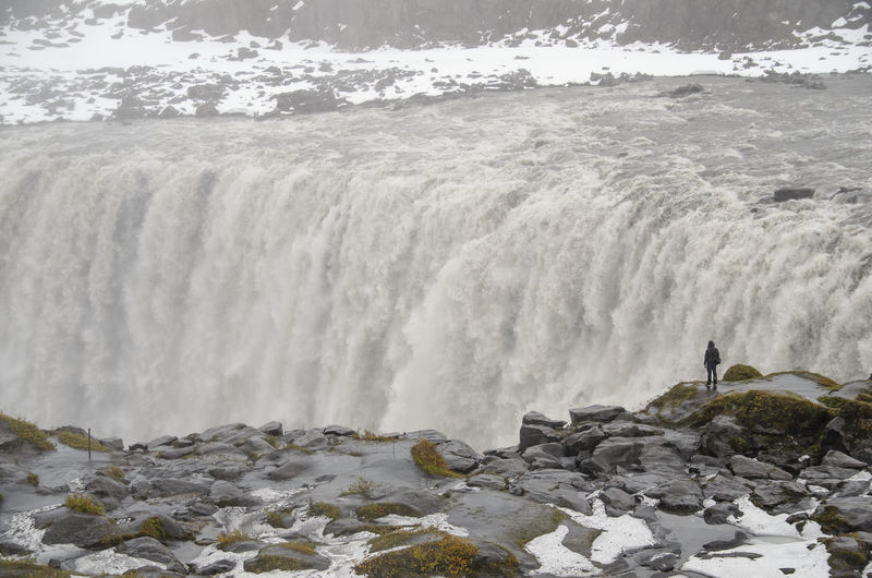 Rear view of person looking at waterfall