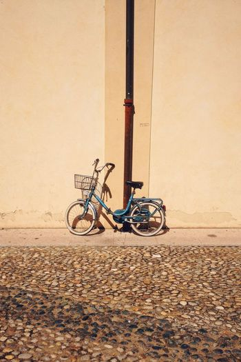 Bicycle parked against wall at cobbled street