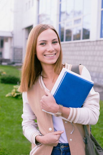 Portrait Of Smiling Young Woman Holding Book While Standing Outdoors