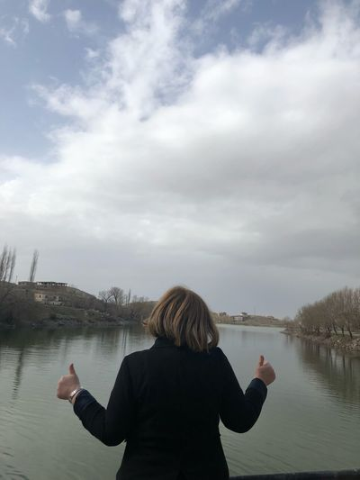 Rear view of woman gesturing thumbs up while standing against lake