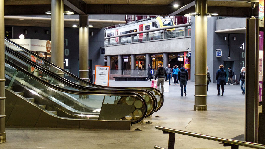 Architecture Built Structure Transportation Real People Incidental People Escalator City Men Indoors  People Railing Lifestyles Mode Of Transportation Staircase Group Of People Day Glass - Material Store Women Modern Architectural Column