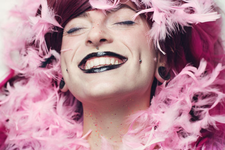 Close-Up Of Woman With Make-Up Smiling Amidst Pink Feathers