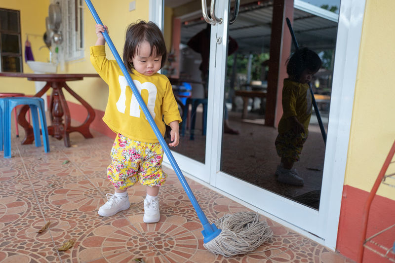 Cute baby girl moping floor at home