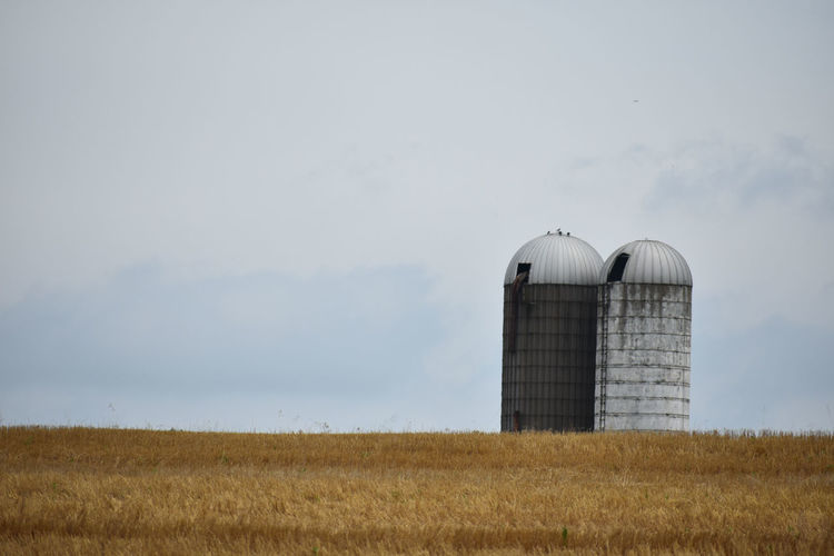Silo on field against sky