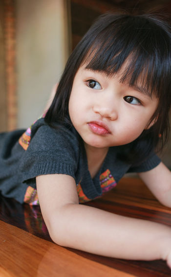 Asian Children Asian Girl Black Hair Casual Clothing Child Childhood Close-up Day Home Interior Indoors  Looking At Camera One Person Portrait Real People Sitting Table