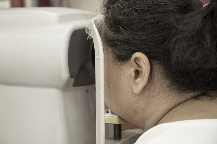 Close-Up Of Woman Looking In Medical Equipment
