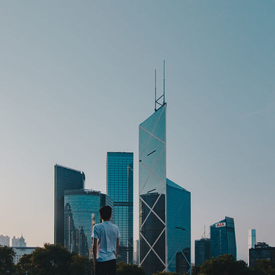 Rear view of man standing by cityscape against clear sky