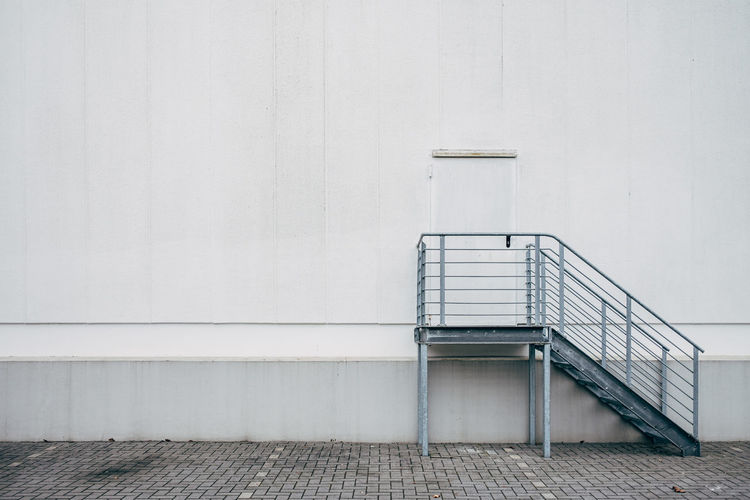 Empty bench against white wall