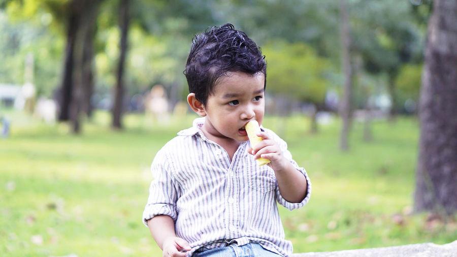 Cute boy eating food in park