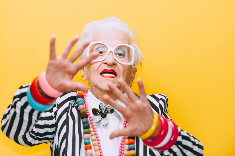 Portrait of senior woman gesturing against yellow background