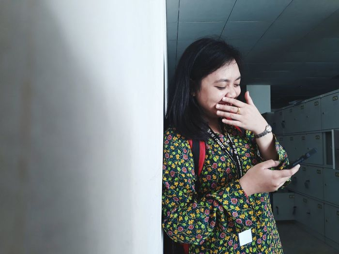 Young woman using phone in locker room