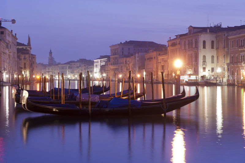 Gondolas moored on grand canal in city at night