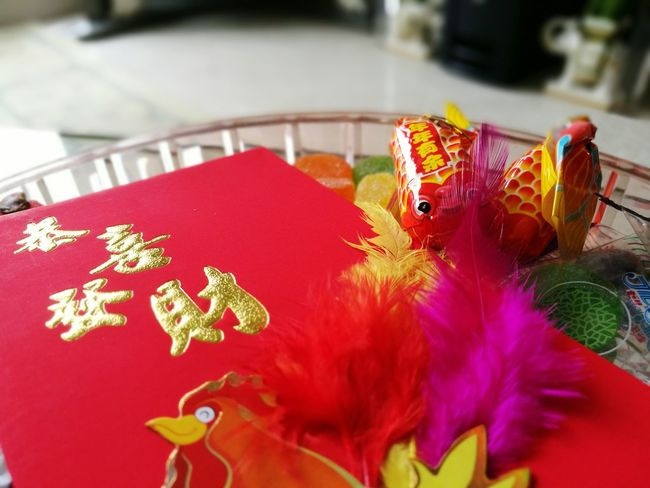 Red Chinese New Year Tradition Cultures Celebration Celebration Event Indoors  Close-up No People Setting The Table Multicolored Candies! Feathers♡ Sweets Red Packet Lunar New Year Colored Feathers Gold Lettering Rooster Rooster Year Full Frame