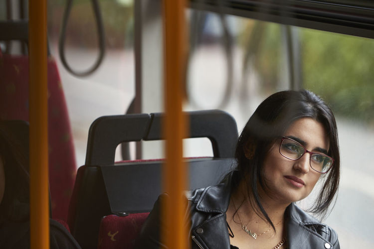 Portrait of young woman sitting in bus
