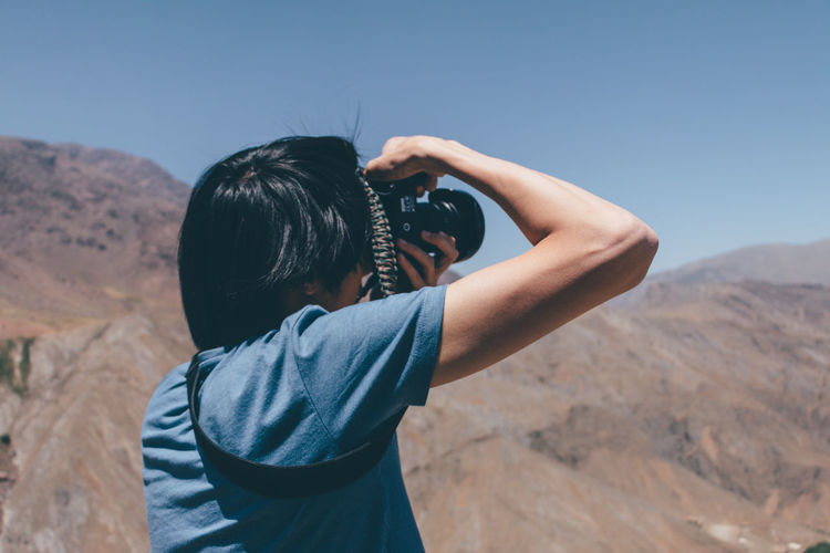 Rear view of man photographing mountains against clear sky