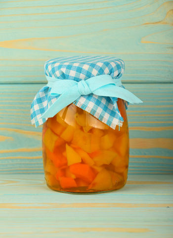 Jar of homemade confiture of pumpkin and quince decorated with blue textile top Blue Bow Confiture Conserve Decorated Diet & Fitness Food Fruit Glass Jar Homemade Jam Jar Pumpkin Quince Ribbon Rustic Wooden